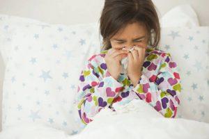 Petite fille dans son lit qui se mouche à cause de son allergie aux acariens