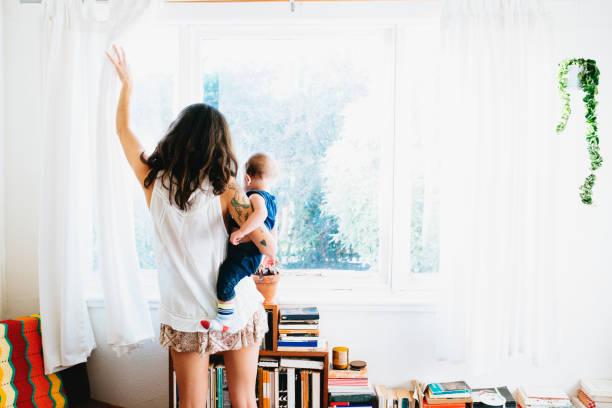 Jeune maman avec son bébé dans les bras qui ouvre la fenêtre pour aérer la chambre à cause des acariens