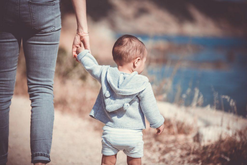 Bébé qui apprend à marcher en tenant sa mère par la main