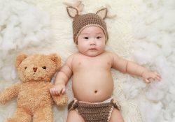 Bébé avec son doudou en ours en peluche